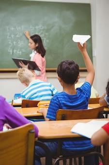 Estudante prestes a lançar um avião de papel