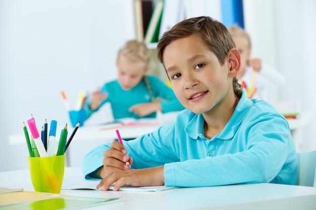 Estudante primário segurando um lápis