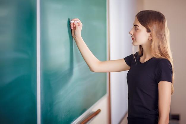 Estudante que está na frente do quadro-negro em branco da classe com um pedaço de giz em sua mão.