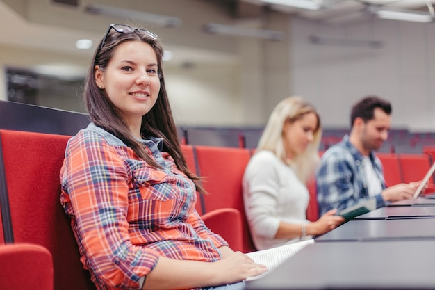 Estudante que olha a câmera na palestra