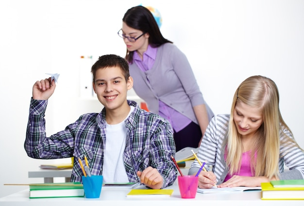 Estudante que prende um avião de papel