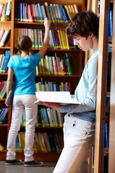 Estudante que prende um livro na biblioteca