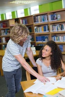 Estudante recebendo ajuda do colega na biblioteca