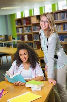 Estudante recebendo ajuda do tutor na biblioteca