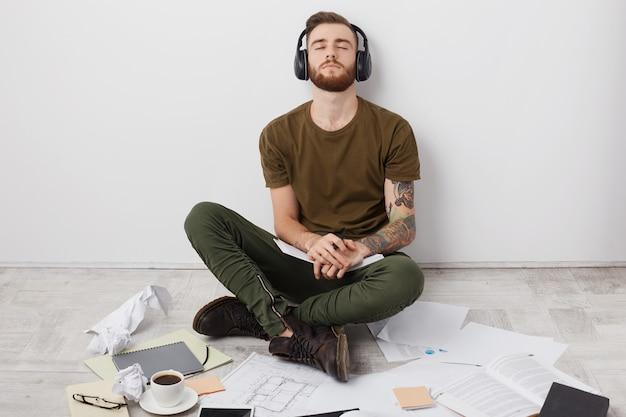 Estudante relaxado e moderno em roupa casual, senta-se no chão de pernas cruzadas, curte rock em fones de ouvido,