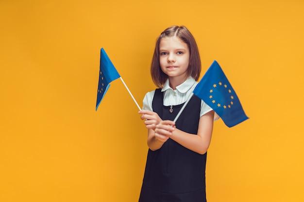 Estudante segurando duas pequenas bandeiras da união europeia nas mãos, educação no conceito de europa