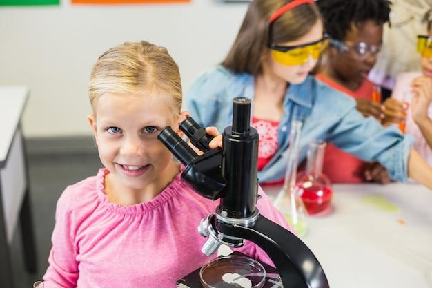 Estudante segurando o microscópio no laboratório