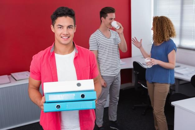 Estudante segurando pilha de pasta de anel perto de colegas de classe com café
