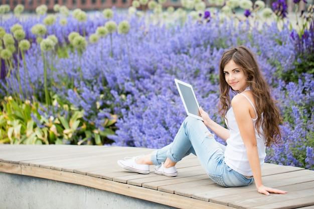 Estudante segurando um touchpad no parque