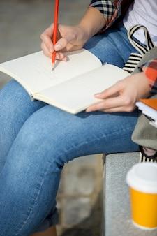 Estudante senhora escrevendo em um caderno aberto com um lápis