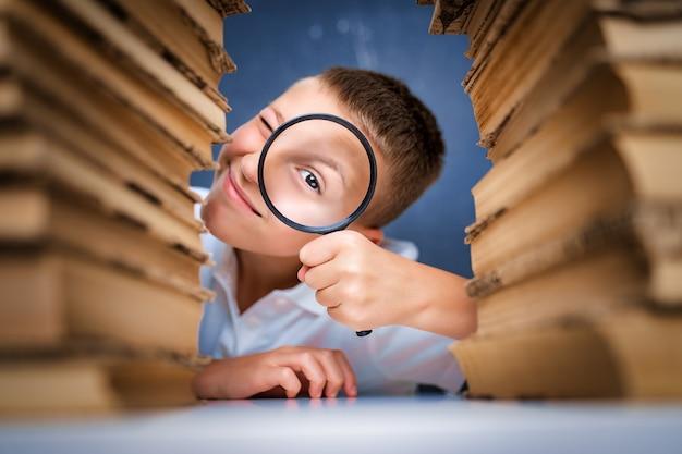 Estudante sentado entre duas pilhas de livros, olhando para a câmera através da lupa.
