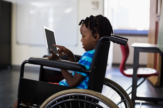 Estudante sentado na cadeira de rodas e usando tablet digital