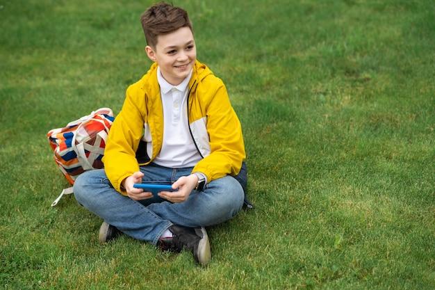 Estudante sentado no gramado com o telefone