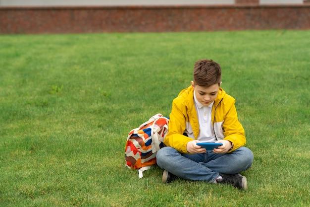 Estudante sentado no gramado com um smartphone Foto Premium
