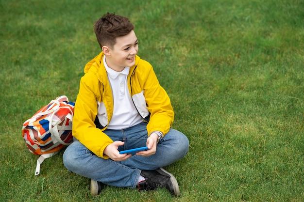 Estudante sentado no gramado com um smartphone