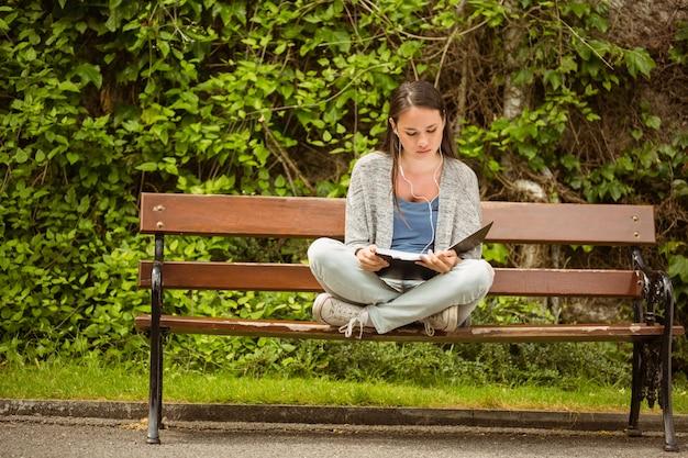 Estudante, sentar-se banco, escutar música, com, telefone móvel, e, revisar, em, parque, em, escola