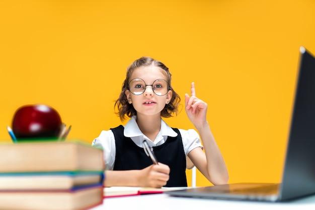 Estudante séria levanta o dedo sentado na mesa com o laptop em educação a distância de óculos