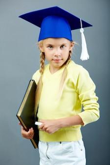 Estudante sério com boné e giz graduação
