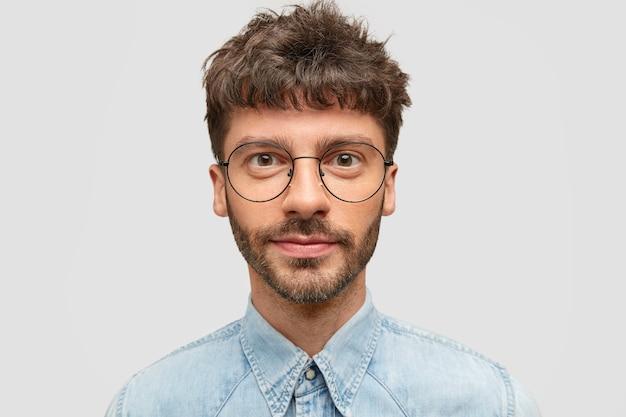 Estudante sério e confiante de homem com a barba por fazer, usando óculos e camisa da moda jeans, ouve informações sobre o exame com atenção