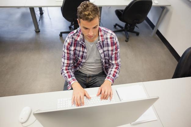 Estudante severo bonito trabalhando no computador