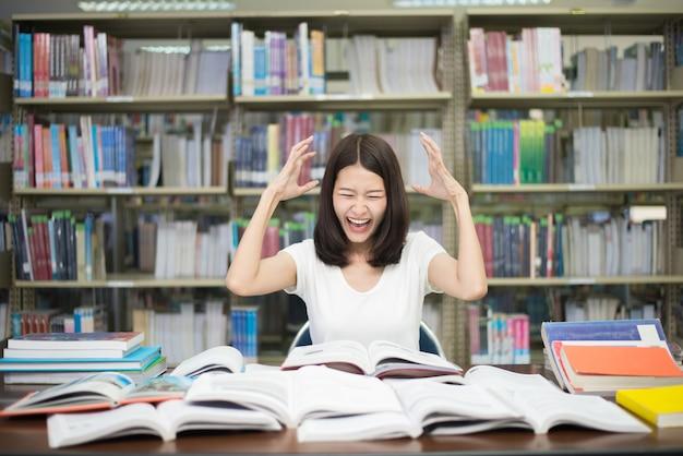 Estudante sob pressão mental enquanto lendo livro preparando o exame em biblioteca na universidade.