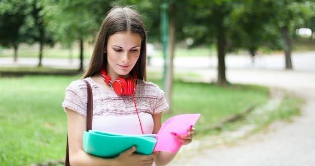 Estudante sorridente ao ar livre, lendo um livro