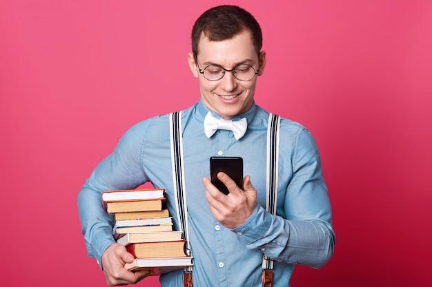 Estudante sorridente com pilha de livros, camisa em um tom, suspensórios e gravata borboleta