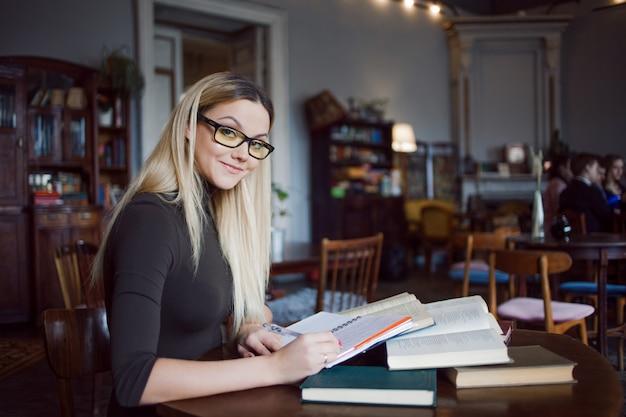 Estudante sorridente da universidade. preparando lições para o exame e aprendendo na biblioteca pública. sentado à mesa, rodeado por um grande número de livros didáticos