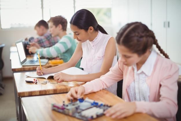 Estudante sorridente fazendo lição de casa na sala de aula
