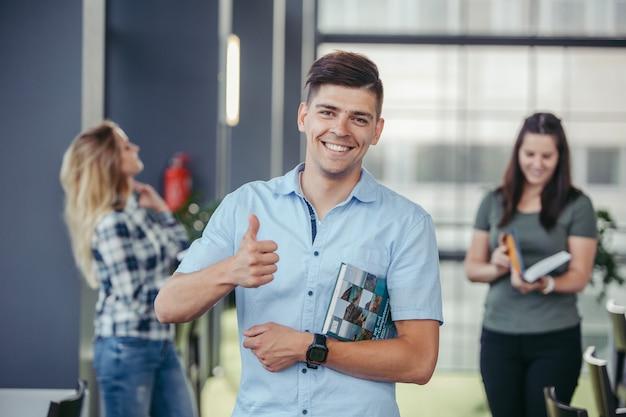 Estudante sorridente gesticulando o polegar para cima