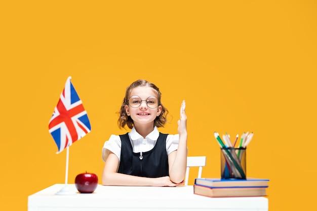 Estudante sorridente levantando a mão sentada na mesa durante a aula de inglês. bandeira da grã-bretanha