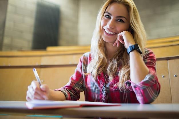 Estudante sorridente posando para a câmera na sala de aula