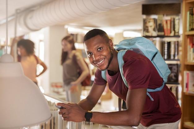 Estudante sorridente segurando uma foto média de smartphone