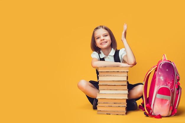 Estudante sorridente, sentada atrás de uma pilha de livros e levantando mão do conceito de aprendizagem e escola