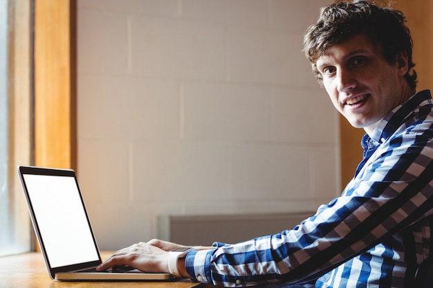 Estudante sorridente usando laptop na faculdade