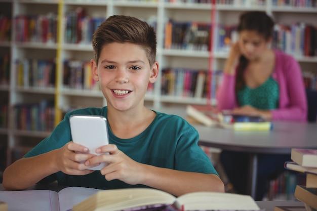 Estudante sorridente usando telefone celular na biblioteca da escola