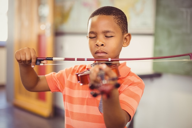 Estudante tocando violino na sala de aula