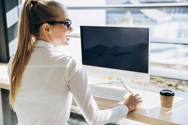 Estudante trabalha com um computador pessoal na biblioteca