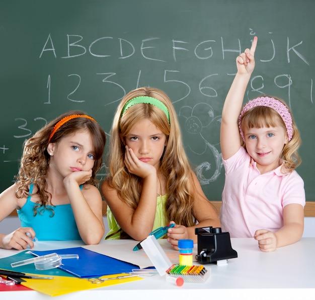 Estudante triste chato com as crianças inteligentes menina levantando a mão