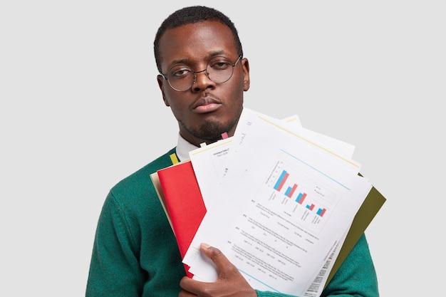 Estudante triste, sonolento, pele escura, tem uma aparência sombria, carrega documentos, trabalhou no relatório financeiro a noite toda