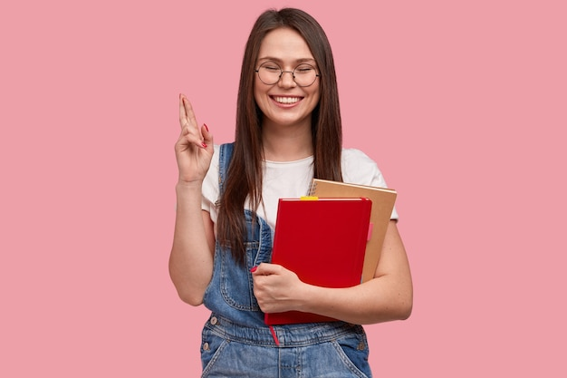 Estudante universitária com olhar feliz, cruza os dedos para dar sorte na prova, segura um caderno para escrever registros, vestida de macacão jeans