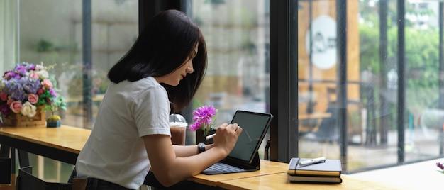 Estudante universitária fazendo trabalho com mesa digital simulada em um café