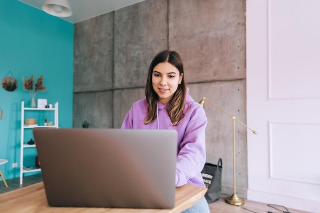 Estudante universitária jovem estudando com laptop, preparando-se à distância para o exame de teste, escrevendo ensaio fazendo lição de casa em casa, conceito de educação à distância.