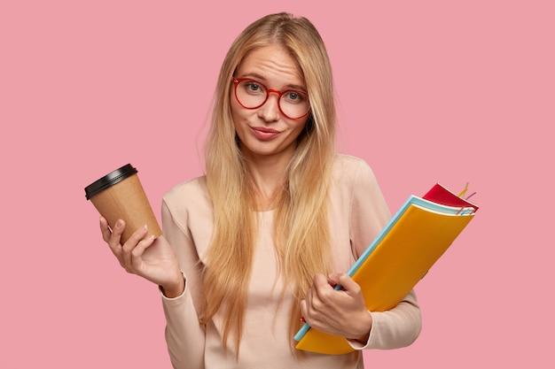 Estudante universitária loira sem noção posando contra a parede rosa