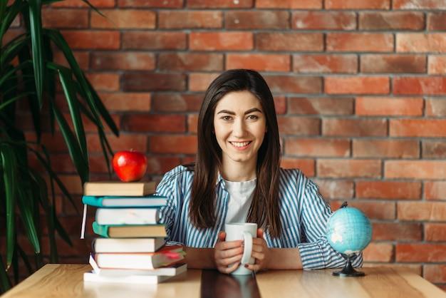 Estudante universitária sentada à mesa com livros didáticos e maçã no topo