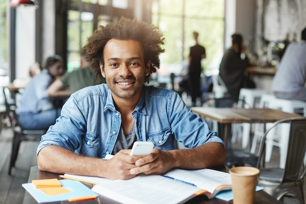 Estudante universitário afro-americano carismático e bonito, com barba, usando conexão sem fio à internet em seu dispositivo eletrônico durante a hora do almoço