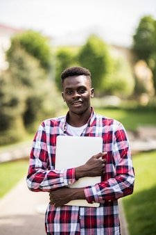 Estudante universitário afro-americano com laptop em um dia ensolarado na rua da cidade