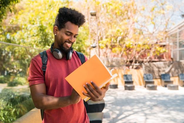 Estudante universitário afro estudando e lendo seu livro