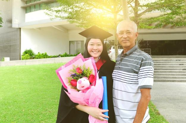 Estudante universitário asiática e pai comemorando a formatura ao ar livre