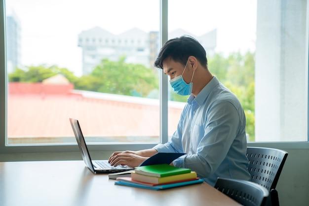 Estudante universitário asiático usando máscara protetora médica para proteção